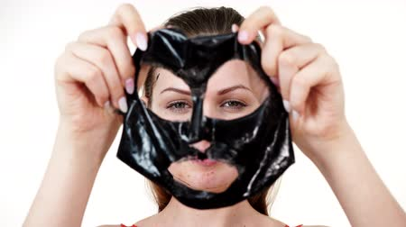 Girl removes black mask from face Dostupné videozáznamy