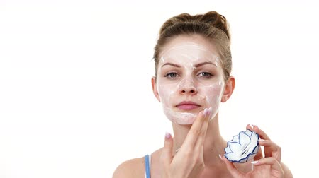 Woman applying mask cream on face