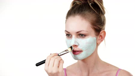 Girl apply white green mud mask to face