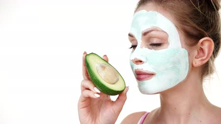 Girl mud mask on face holds avocado fruit