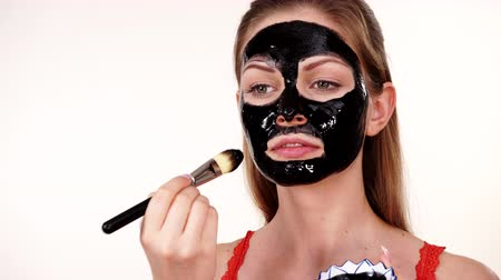 Girl applying black carbo mask to face Filmati Stock