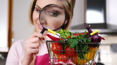 Woman magnifying vegetables in basket