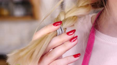 Woman playing with blonde braid hair
