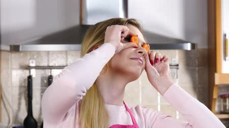 Funny woman playing with carrots on eyes