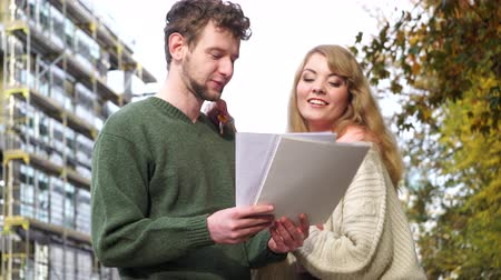 properties : Couple on front of new house with blueprint project 4K Stock Footage