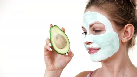 clay mask : Girl mud mask on face holds avocado fruit