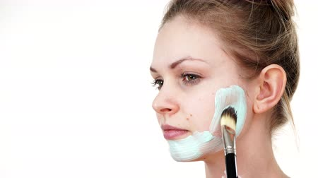 clay mask : Girl apply white green mud mask to face