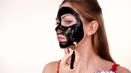 clay mask : Girl applying black carbo mask to face Stock Footage