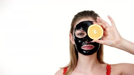 mascarar : Girl black mask on face holds orange fruit