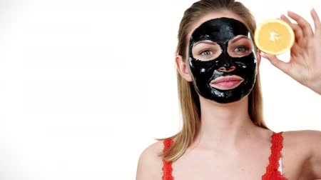 off : Girl black mask on face holds orange fruit