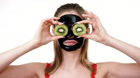 off : Girl black mask on face holds kiwi fruit