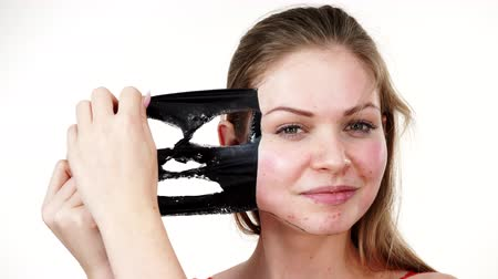 clay mask : Girl removes black mask from face Stock Footage