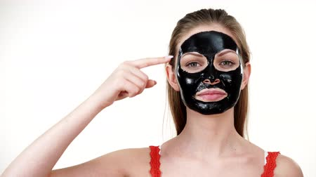 blackhead : Girl with dried peel-off black mask on face Stock Footage