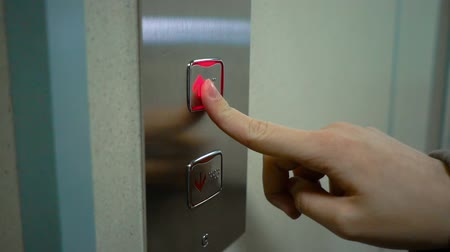 kapualj : Young Woman Presses A Button To Lift To Go Up. Metal elevator. Arrow up. Slow motion. Stock mozgókép