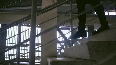 handrails : The girl goes down the stairs, slow motion. The girl goes down the stairs in the Parking lot.
