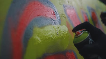 vandalismo : A hand with a spray can that draws a new graffiti on the wall. Graffiti on a wooden wall close-up. Slow motion paint application on the wall.
