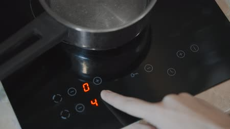 fogão : A close-up of a female hand includes an electric stove. Modern technology. Touch panel of electric cooker. Metal pan stands on the touch plate.