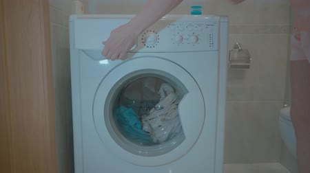wäschetrockner : Womam is gently putting colourful laundry into washing machine. A young girl closes the door of the washing machine foot. 4k video. Videos