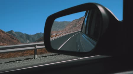 kilometer : Rearview mirror gray car. Back view of the car mirror Mountains and desert in the background.