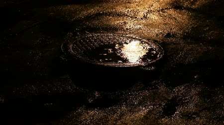 sulky : Manhole in the puddle from night rain Stock Footage