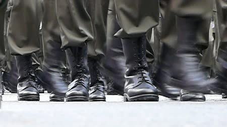 Black boots of soldiers marching on asphalt of square