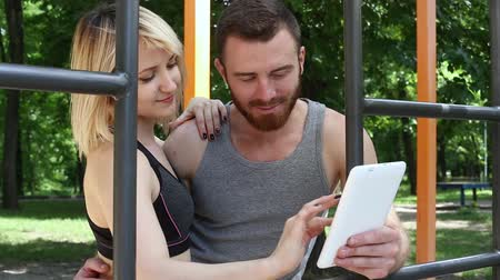 barbate : Young caucasian woman and a bearded man browsing the internet on a white tablet. Stock Footage