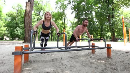 barbate : Young sportive woman and bearded man doing push-ups in the morning. Stock Footage