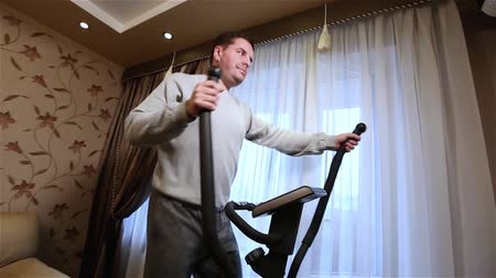 elliptical : Adult caucasian man doing exercises on cardio at home. Stock Footage