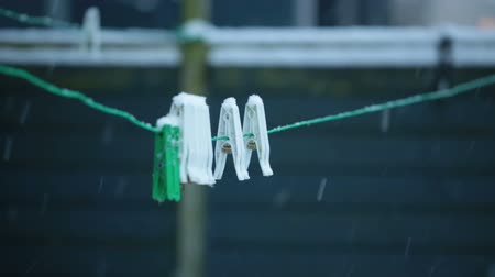prendedor de roupa : Plastic laundry clothes pins or clips in a snowy day Stock Footage