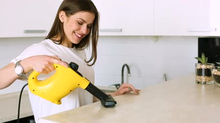 caucasiano : Woman cleaning kitchen with steam cleaner
