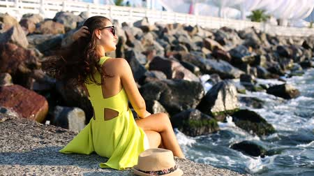 Beautiful young woman sitting on the pier Stock Footage