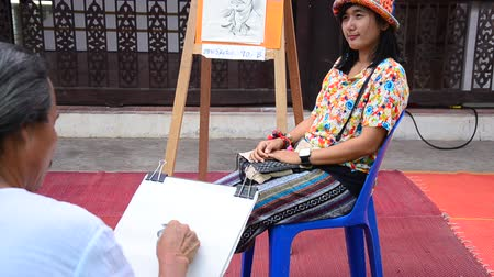 ratchaburi : Old man artist drawing and sketch thai woman for exchange with money at Wat Khanon in Ratchaburi Thailand.