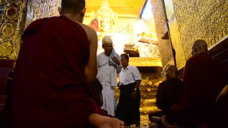 budist : Monks wash the face and brush the teeth of Maha Myat Muni Buddha image statue Stok Video
