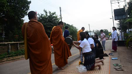 szerzetes : Monk walking on the road for people pray and put food offerings to Buddhist alms bowl at morning time at Phu Thai Ethnic group at Ban None Hom village in  Sakon Nakhon, Thailand