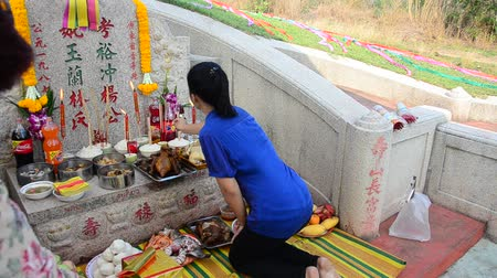 ratchaburi : Thai woman praying graveyard of Ancestor Worshipping in the Qingming Festival at graveyard in Sritasala Cemetery in Ratchaburi, Thailand. Stock Footage