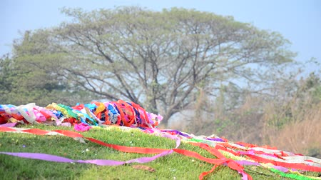 ratchaburi : Wind and moving of colored paper on a grave in process of ceremony  in Qingming Festival at Sritasala Cemetery in Ratchaburi, Thailand.