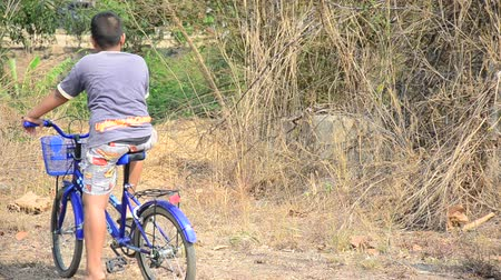 ratchaburi : Thai boy riding bicycle near graveyard in Sritasala Cemetery in Ratchaburi, Thailand. Stock Footage