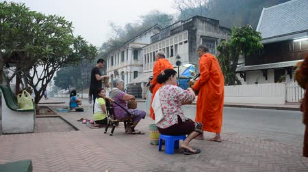prabang : Tradition of almsgiving with sticky rice by Monks procession walk on the road for people put food offerings at Wat xieng thong in Luang Prabang, Laos