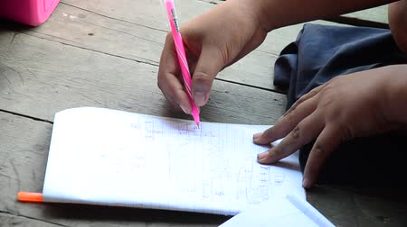 samut : Thai children study and writing homework on notebook at wooden table in house in Samut Sakhon, Thailand