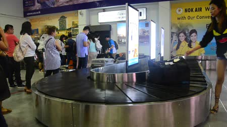 aguardando : Thai people and traveller wait receive luggage on carousel conveyor at Trang International Airport in Trang, Thailand Stock Footage