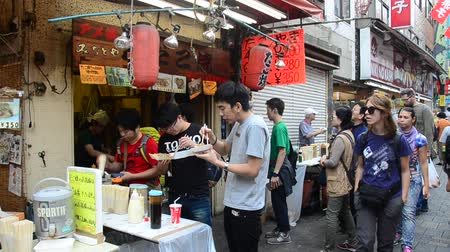 kuyruk : Japanese people and travelers foreigner standing queue buy takoyaki is a ball-shaped japanese snack at shop in Ameyoko market at Ueno in Tokyo, Japan Stok Video