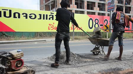 compactor : Thai people use soil compactors in construction site working and repair surface of road at rural roads countryside in Nonthaburi, Thailand Stock Footage
