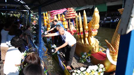 Thai people praying and put food offerings monks in traditional procession by boat in Sainoi canal at Wat Sai Yai in Nonthaburi, Thailand. Dostupné videozáznamy