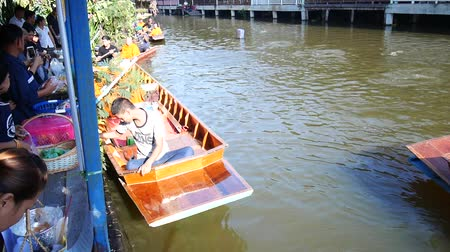procession : Thai people praying and put food offerings monks in traditional procession by boat in Sainoi canal at Wat Sai Yai in Nonthaburi, Thailand. Stock Footage