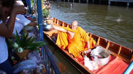 Thai people praying and put food offerings monks in traditional procession by boat in Sainoi canal at Wat Sai Yai in Nonthaburi, Thailand. Stok Video