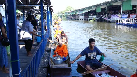 заслуга : Thai people praying and put food offerings monks in traditional procession by boat in Sainoi canal at Wat Sai Yai in Nonthaburi, Thailand. Стоковые видеозаписи