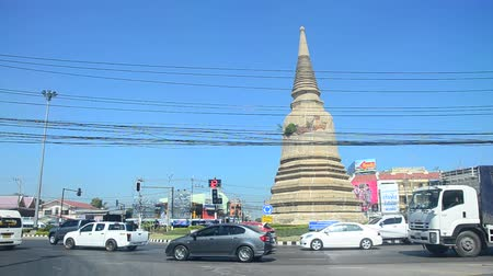 Thai people drive vehicle on traffic road go to work and visit archaeological site at roundabout ancient chedi in Ayutthaya, Thailand