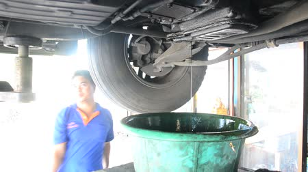Thai mechanic people and professional automotive motor repair and maintenance change oil, Oil Filter and Check availability and prepare of car at local garage shop in Nonthaburi, Thailand