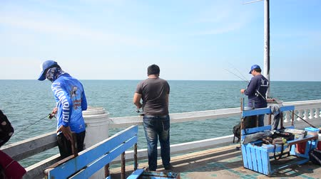 Thai men standing and fishing or angling in sea at Laem Thaen Cape in Bang Saen Beach in Chonburi, Thailand