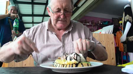 German old man eating Honey and chocolate lava on waffles with vanilla ice cream and banana and whipped cream in market in Nonthaburi, Thailand